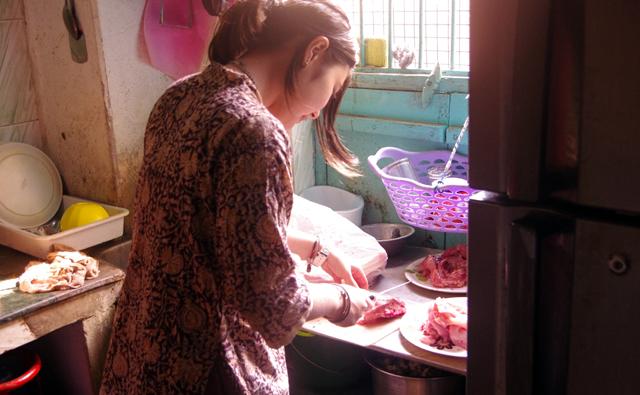 キッチンで肉を切る