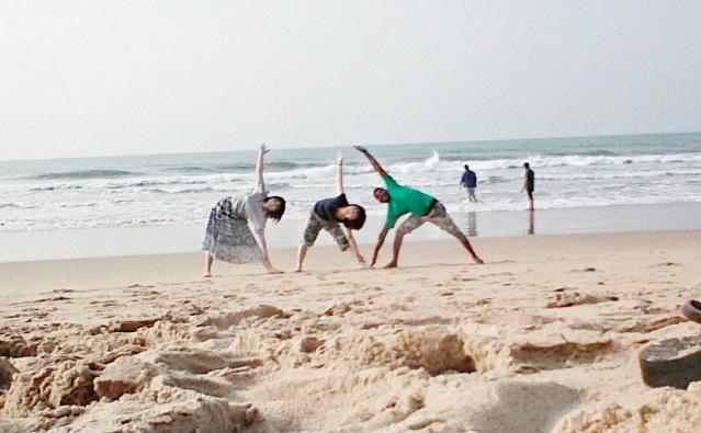 インドのビーチでヨガ仲間とポーズ
