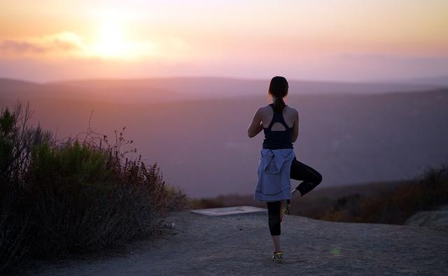 夕日を眺めながらヨガ、アーサナをする女性