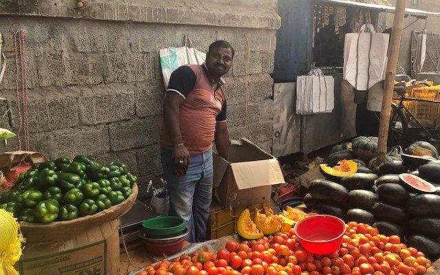 路上で野菜をうる男性