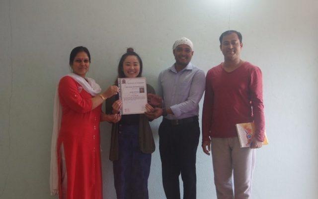 ヨガホールでインド人講師から修了書を受け取る