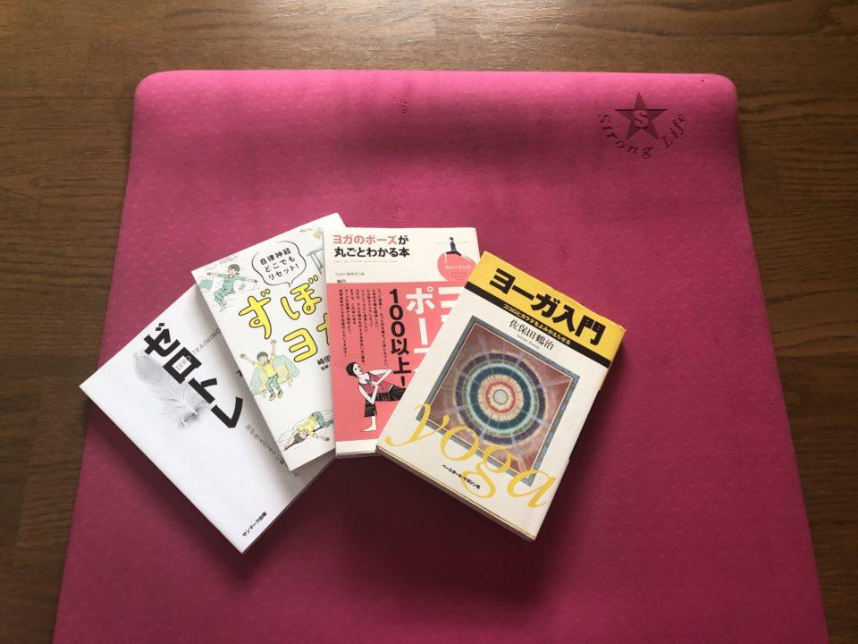 ヨガマットの上にヨガの本が4冊並べている写真
