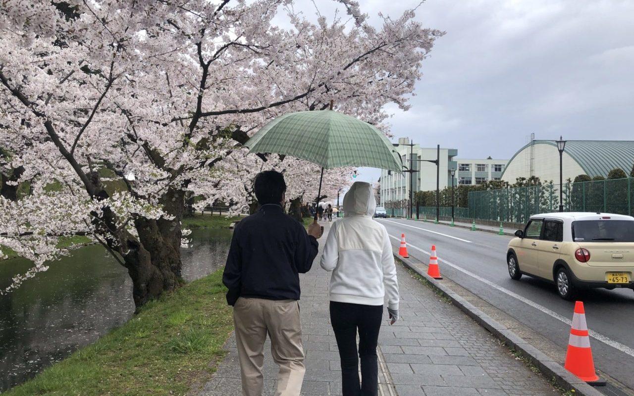中年夫婦があいあい傘をして歩いている写真